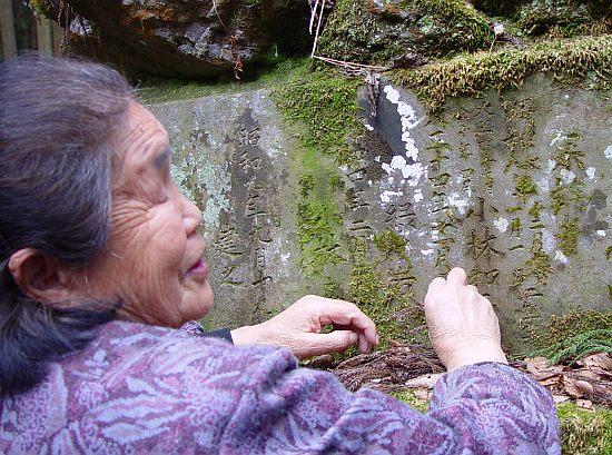 小林和平の銘のあたりを一生懸命こすっている地元のおばあさん